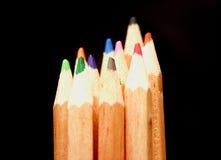 Matite di colore sui precedenti neri fotografia stock