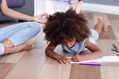 Matite di disegno della ragazza afroamericana graziosa mentre meditare della madre fotografie stock