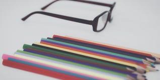 Matite e vetri di colore sullo scrittorio Fotografie Stock