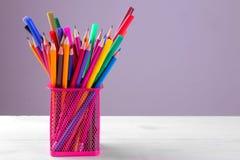 Matite multicolori ed indicatori in un vetro per le matite su un fondo grigio immagine stock