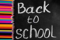 Matite multicolori su un consiglio scolastico nero con l'iscrizione di nuovo alla scuola fotografie stock libere da diritti