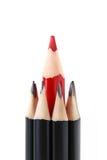 Matite nere con rossa nel mezzo Fotografia Stock