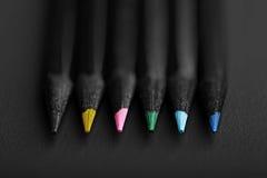 Matite nere e colorate, su fondo nero, profondità bassa del fi Fotografie Stock Libere da Diritti