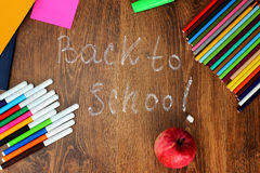 Matite, pennarelli ed indicatori colorati, taccuini, autoadesivi una mela rossa sui precedenti di legno con di nuovo a Immagine Stock Libera da Diritti