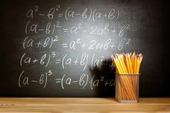 Matite su uno scrittorio di legno della scuola davanti ad una lavagna nera con la scuola di formule matematiche Concetto di forma Immagine Stock Libera da Diritti