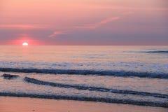 Matizes cor-de-rosa e roxos com o sol que espreita sobre o horizonte do nascer do sol do oceano Imagens de Stock