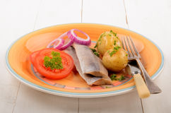 Matjes herring and boiled potatoes with tomato on a plate Stock Photo