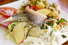 Matjes herring with yoghurt dressing, fruits and fried potatoes Royalty Free Stock Photos