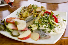 Matjes herring with yoghurt dressing, fruits and fried potatoes Stock Image