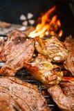 Matkött - bli rädd och gnälla på galler för partisommargrillfest Arkivfoton