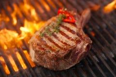 Matkött - nötköttbiff på bbq-grillfestgaller med flamman royaltyfri foto