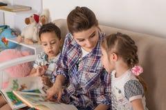 Matka angażuje z dziećmi Matka z małymi dziećmi czytającymi Obraz Royalty Free