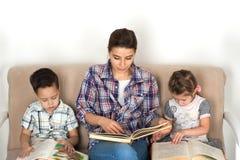 Matka angażuje z dziećmi Matka z małymi dziećmi czytającymi Fotografia Royalty Free