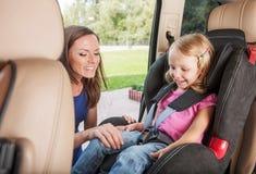 Matka bierze opiekę o jej córce w samochodzie obraz stock