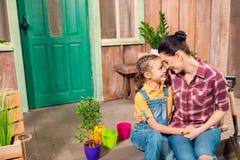 Matka, córki mienie i obsiadanie ręki na ganeczku z doniczkowymi roślinami i zdjęcie stock
