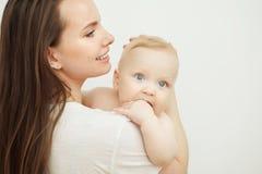 Matka całuje dziecka w policzku, dziecko odpoczynki na mamy ramieniu obrazy stock