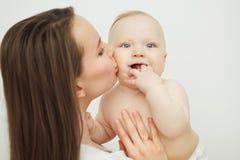 Matka całuje jej dziecka, dziecko chwyty jego palec blisko usta zdjęcie royalty free