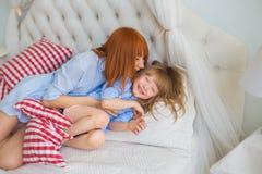 Matka całuje jej małej córki na łóżku w ranku Zdjęcie Stock
