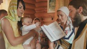 Matka chrzestna ciosy na jej chrześniaku podczas księdza recytują modlitwę zdjęcie wideo