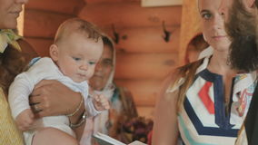 Matka chrzestna trzyma chrześniaka w rękach podczas księdza recytuje modlitwę zbiory wideo