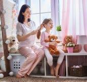 Matka czesze jej córki ` s włosy Fotografia Royalty Free