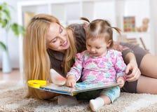 Matka czyta książkę żartować w domu zdjęcie royalty free