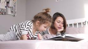 Matka czyta książkę dla jej dwa córek kłama na łóżku Identyczny odziewa zbiory