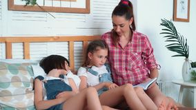 Matka czyta książkę jej córki i spadają uśpiony na łóżku, szczęśliwa rodzina zbiory