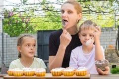 Matka, dwa córki liże łyżki z ciasteczka lodowaceniem dla Wielkanocnych babeczek Zdjęcia Royalty Free