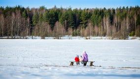 Matka, dwa małych dziewczynek obsiadanie w ławce Fotografia Royalty Free