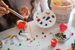 Matka i córka przygotowywamy dla wielkanocy Trzymają muśnięcia i dostają niektóre farba kolor dla jajek Cukierki w pucharze Kosz  obrazy royalty free