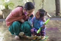 Matka i córka świętuje Holi festiwal kolory Fotografia Stock