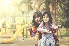 Matka i córka bawić się mydlanych bąble przy boiskiem zdjęcia royalty free