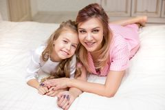 Matka i córka bawić się na łóżku wpólnie zdjęcia royalty free