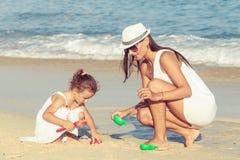 Matka i córka bawić się na plaży przy dnia czasem Obraz Royalty Free