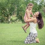 Matka i córka bawić się na trawie przy dnia czasem Zdjęcie Royalty Free