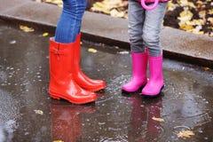 Matka i córka jest ubranym gumowych buty stoi w kałuży na deszczowym dniu, ostrość nogi obraz royalty free
