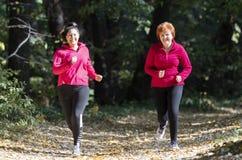 Matka i córka jest ubranym sportswear i bieg w lesie zdjęcia stock