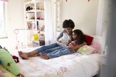 Matka I córka Jest usytuowanym Na Łóżkowej Używa Cyfrowej pastylce Zdjęcie Royalty Free