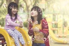 Matka i córka ma zabawę z mydlanymi bąblami przy boiskiem Zdjęcie Stock