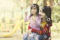 Matka i córka ma zabawę z mydlanymi bąblami przy boiskiem obrazy stock