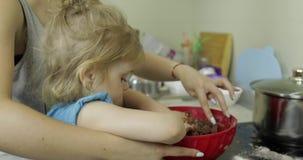 Matka i córka miesza czekoladowego ciasto, dziewczyna robi tortowi w kuchni zbiory wideo