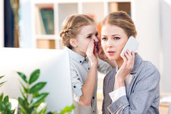 Matka i córka opowiada w biznesowym biurze, bizneswoman używa smartphone fotografia stock
