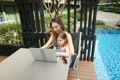 Matka i córka pracuje wpólnie use laptop na tle zdjęcia royalty free
