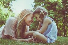 Matka i córka siedzi wpólnie na zielonej trawie Matka i zdjęcie stock
