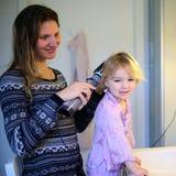 Matka i córka szczotkuje włosy wpólnie obraz stock