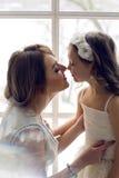 Matka i córka trzy roku siedzi wielkim okno Zdjęcia Stock