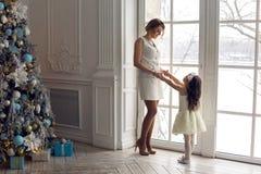 Matka i córka trzy roku stoi wielkim okno Obraz Royalty Free