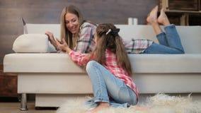 Matka i córka używa w domu laptop i telefon zbiory