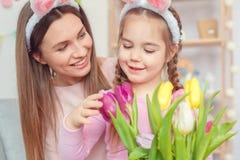 Matka i córka w królików ucho Easter świętowaniu patrzeje tulipany wpólnie w domu Zdjęcie Royalty Free